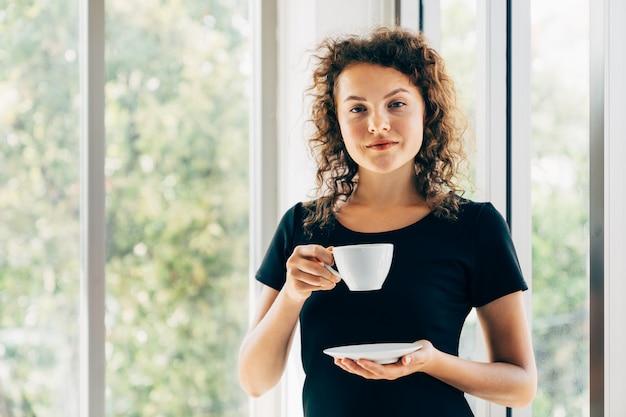 ホームオフィスの窓の横にコーヒーを飲みながらリラックスして笑顔で立っている若いカジュアルなビジネス女性の肖像画の画像