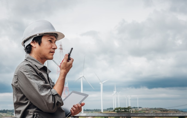 Portrait images of an asian engineer, technician man standing, holding a tablet and using  radio communication, with wind turbines, to people and electricity production concept.