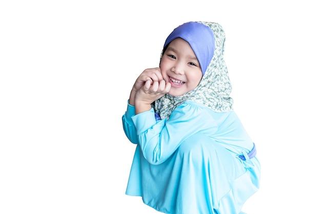 青いイスラムのドレスを着て、座っている4歳のアジアの女の子の肖像画の画像