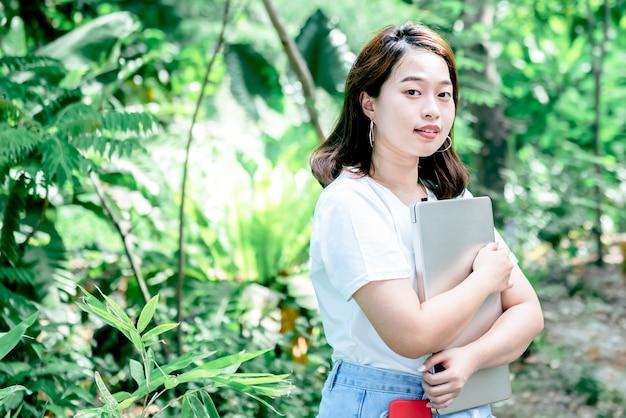 Портретные изображения азиатской привлекательной женщины, стоящей и держащей ноутбук