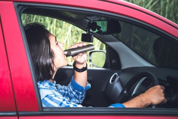 아시아 남자가 운전하는 동안 술을 마시고 있는 초상화 이미지