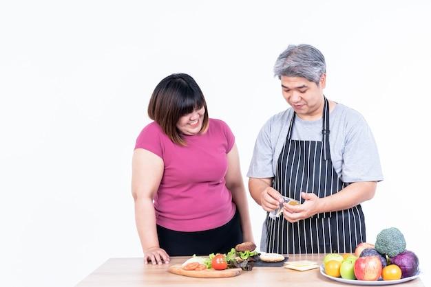 햄버거를 요리하기 위해 웃고 있는 동양인 아내와 남편 비만의 초상화 이미지
