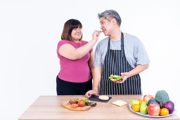 Портретные изображения азиатской жены и мужа тучные улыбаются и радуются съесть гамбургер, который она приготовила на белом фоне, азиатской семье и концепции быстрого питания.