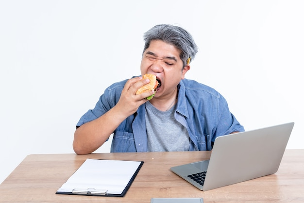 Портретные изображения деловых людей среднего возраста. азиатские мужчины едят гамбургеры. в то время как он работал с использованием портативного компьютера для деловой работы, людей и концепции питания.