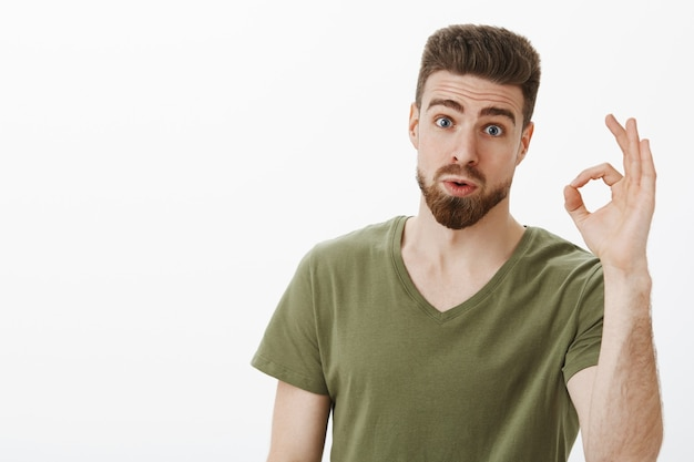 Portrait of impressed guy checking out awesome idea of friend saying wow and not bad showing okay gesture raising eyebrows as being amazed with nice plan posing astonished over white wall