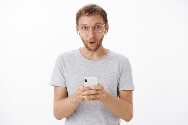 Ritratto di ragazzo caucasico bello colpito con setola dicendo wow con sorriso soddisfatto che tiene smartphone indossando auricolari
