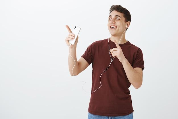 Ritratto del ragazzo felice bello impressionato in maglietta rossa