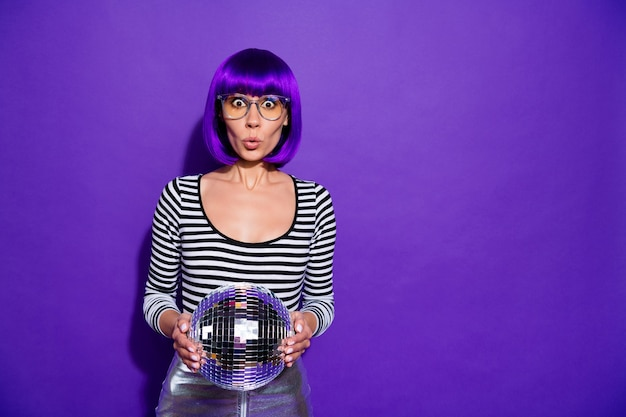 Portrait of impressed lady with eyewear eyeglasses holding mirror ball isolated over purple violet background