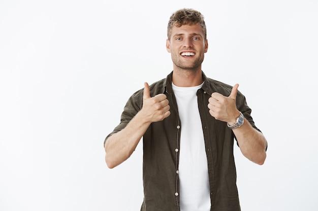 Ritratto di un amico maschio impressionato e compiaciuto con un sorriso affascinante che mostra il pollice in su in allegria e supporto, totalmente d'accordo e soddisfatto dell'eccellente scelta sul muro grigio