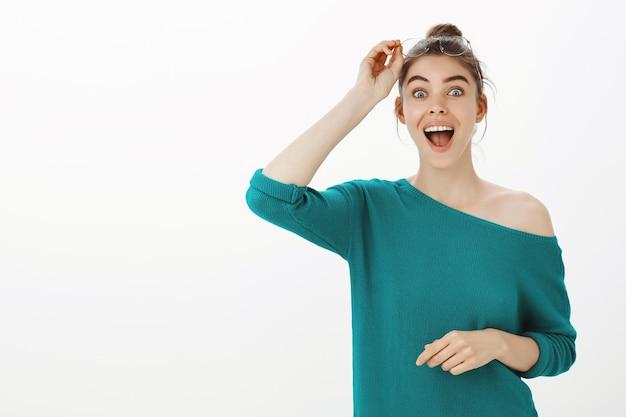 Ritratto di occhiali da decollo colpiti e sorpresi della giovane donna e sorridenti dallo stupore
