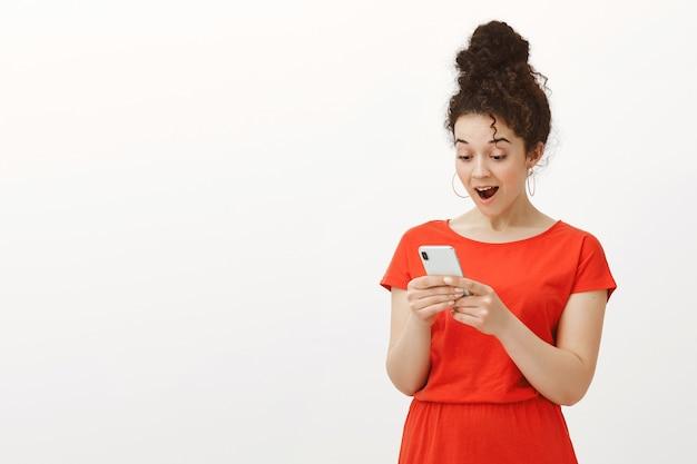 Ritratto della studentessa attraente entusiasta impressionata in vestito rosso alla moda e orecchini rotondi