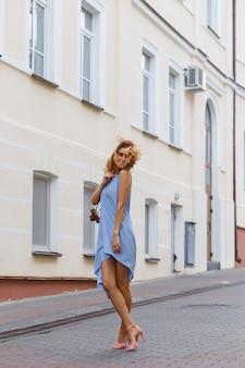 Портрет в полный рост, молодая красивая темно-блондинка в синем платье на улице