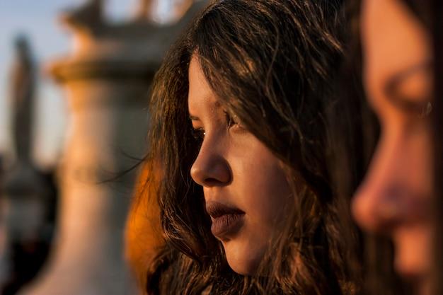 일몰의 따뜻한 빛에 의해 조명 된 어린 소녀의 프로필 근접 촬영에서 초상화.