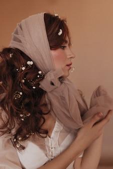 ベージュの背景にポーズをとって黒髪の花を持つ巻き毛の女性のプロファイルの肖像画。