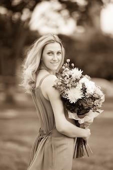 복고 스타일의 초상화입니다. 꽃다발을 들고 웃고 있는 젊은 여성