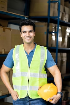 Portrait of indian asian warehouse worker with safety vest stand and hold yellow helmet