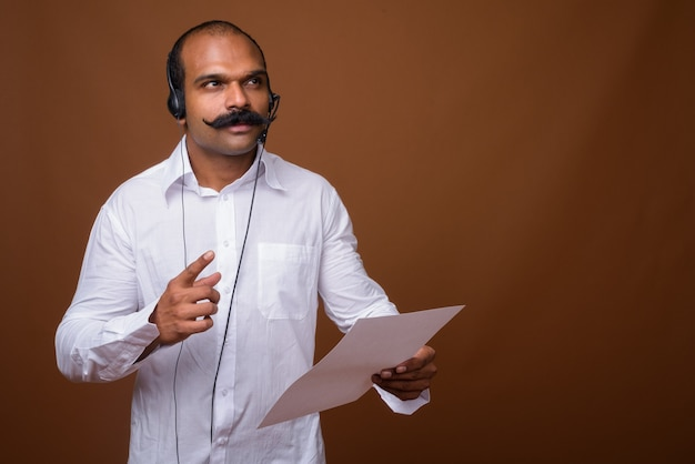 Portrait of indian businessman with mustache as call center representative