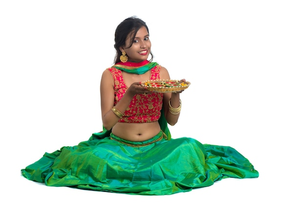 Portrait of an indian traditional girl celebrating diwali or deepavali holding oil lamp during the festival of light on white