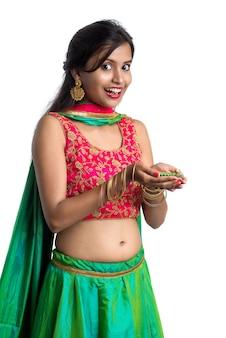 Portrait of a indian traditional girl holding diya and celebrating diwali or deepavali