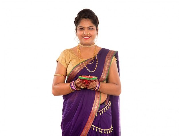 Portrait of a indian traditional girl holding diya, diwali or deepavali photo with female hands holding oil lamp during festival of light on white space
