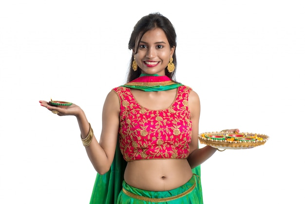 Portrait of a indian traditional girl holding diya, girl celebrating diwali or deepavali with holding oil lamp during festival of light on white background