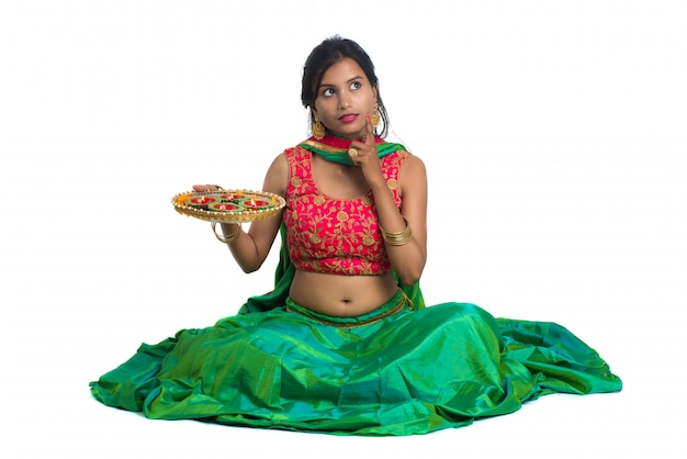Portrait of a indian traditional girl holding diya, girl celebrating diwali or deepavali with holding oil lamp during festival of light on white surface