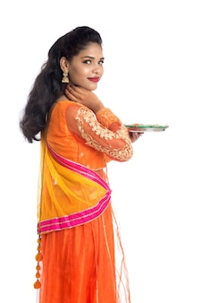 Portrait of a indian traditional girl holding diya, girl celebrating diwali or deepavali with holding oil lamp