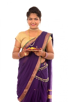 Portrait of a indian traditional girl holding pooja thali with diya during festival of light on white background. diwali or deepavali