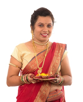Portrait of a indian traditional girl holding pooja thali with diya during festival of light on white