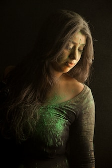 Portrait of indian woman covered in green dust of holi festival