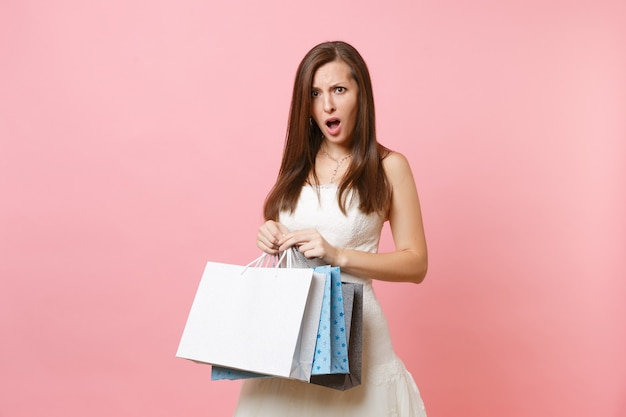Portrait of indignant woman in white dress holding multi colored packages bags with purchases after shopping