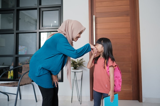 Portrait of indonesian primary school female student shake and kiss her muslim mother's hand before going to school
