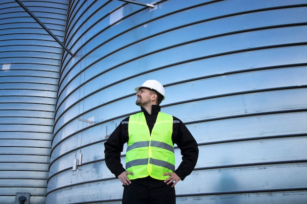 Portrait of industrial worker standing by metal silo storage tank
