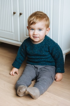 Portrait of infant sits on floor near cupboard, looks with warm blue eyes