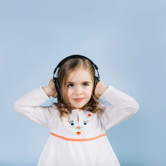 Portrait of a innocence girl listening music on headphone standing against blue background