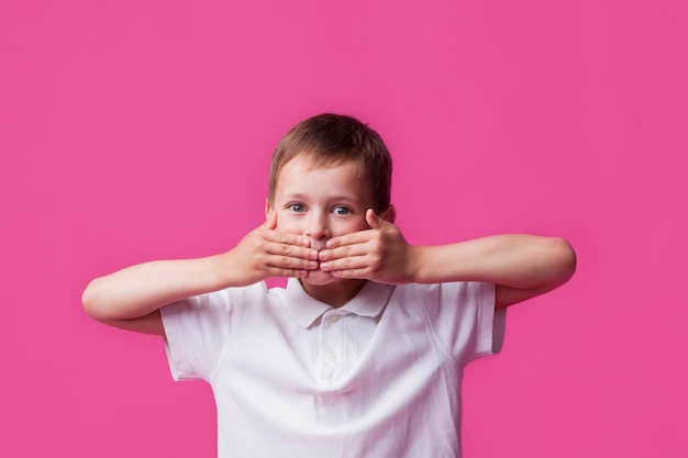 Portrait of innocent boy covering his mouth and looking at camera over pink wall background