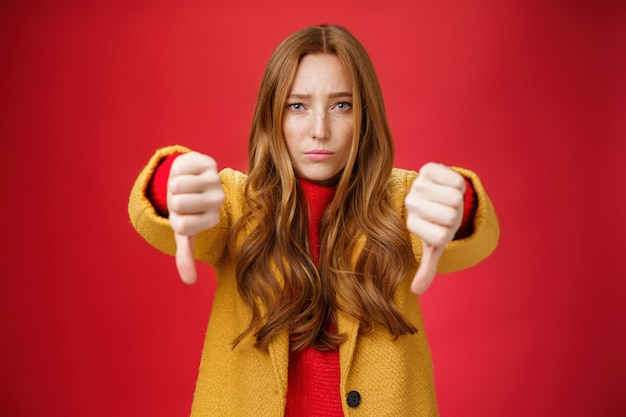 Portrait of insecure and unconfident cute redhead female reacting to uncool thing showing thumbs down with worried upset expression from dislike and disappointment over red background.