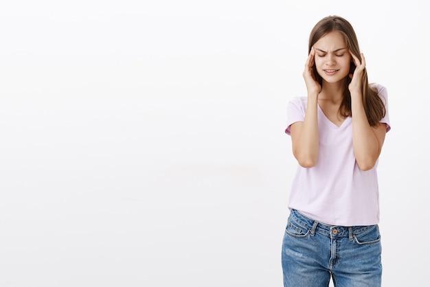 Ritratto di intensa ragazza europea carina con capelli castani chiudendo gli occhi tenendo le mani sulle tempie della testa cercando di concentrarsi e concentrarsi, in piedi sfocato sul muro grigio