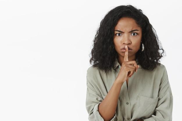 Portrait of intense displeased serious-looking african american woman shushing
