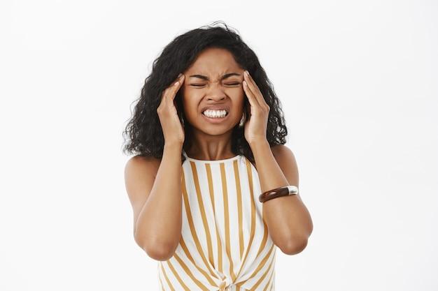 Ritratto di giovane donna afroamericana dispiaciuta intensa che stringe i denti dal dolore