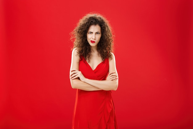 Portrait of intense thoughtful moody woman with curly hairstyle frowning smirking looking from under forehead crossing arms against chest in offended and defensive pose over red background.