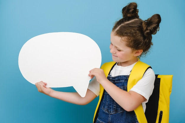 Portrait of interested cheerful kid hold white paper blank speech bubble, thoughts about future weekends, wear stylish yellow backpack, isolated over blue color background in studio. back to school