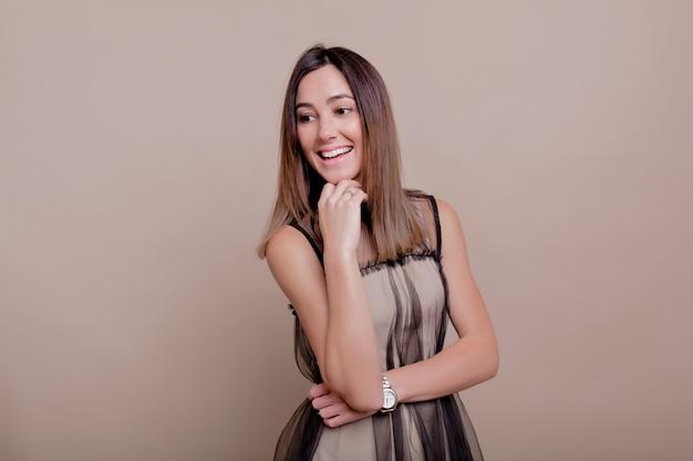 Ritratto di donna interessata con capelli scuri corti e vestito beige vestito sorriso affascinante in posa sul muro beige, posto per il testo, muro isolato