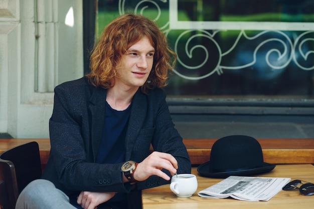 Portrait interesting reddish man mixing coffee