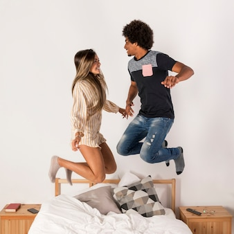 Portrait of interracial couple jumping in bed