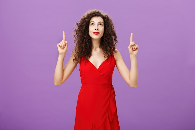 Portrait of intrigued and curious charming young female with curly hairstyle in red stylish evening dress looking and pointing up smiling interested and delighted posing over purple background.