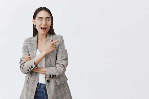 Portrait of intrigued happy european female in glasses and trendy jacket, pointing and looking at upper right corner with amazed and thrilled expression