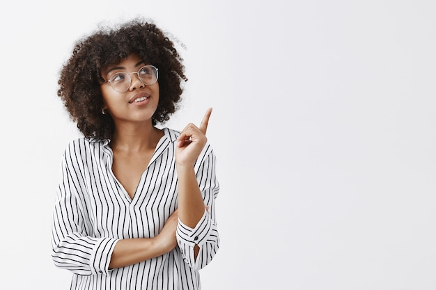 Portrait of intrigued smart and stylish female in striped blouse and glasses looking and pointing at upper right corner with curious interested expression