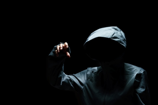 Portrait of invisible man in the hood on black background.