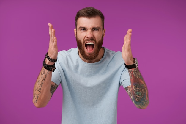 Portrait of irate bearded brunette guy with tattooes raising palms angrily and screaming violently with wide mouth opened, showing negative emotions on purple